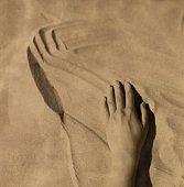 A hand stroking sand